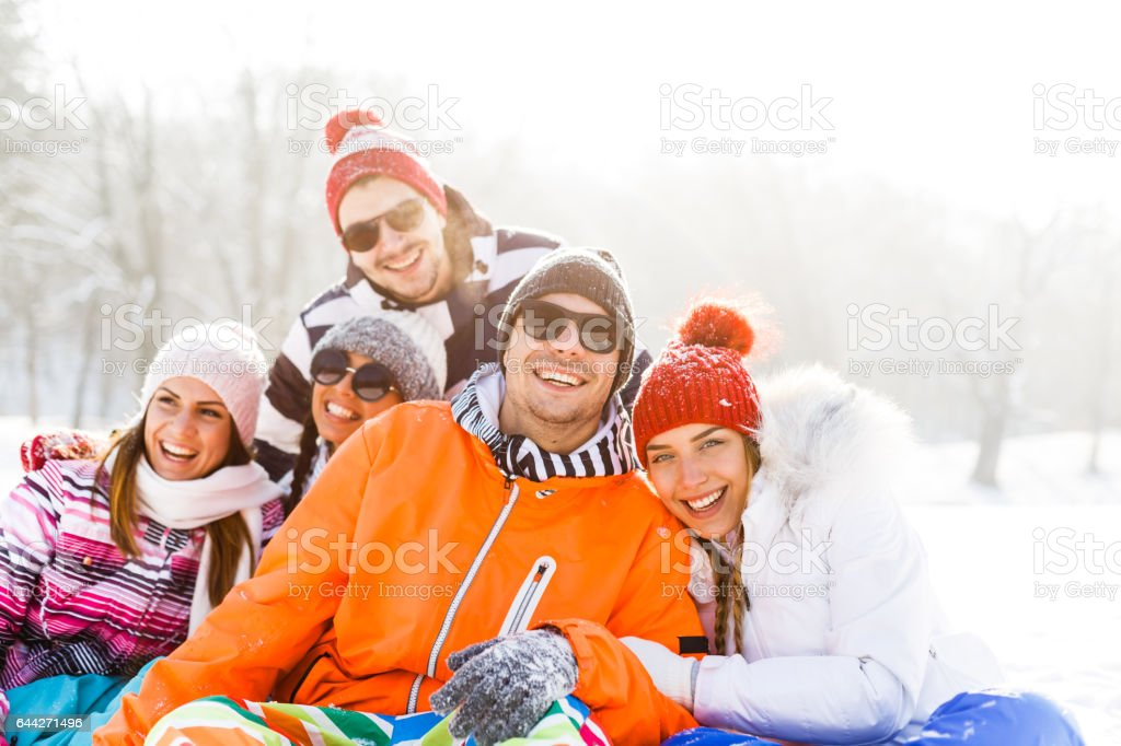 Portrait of happy young friends in snow stock photo
