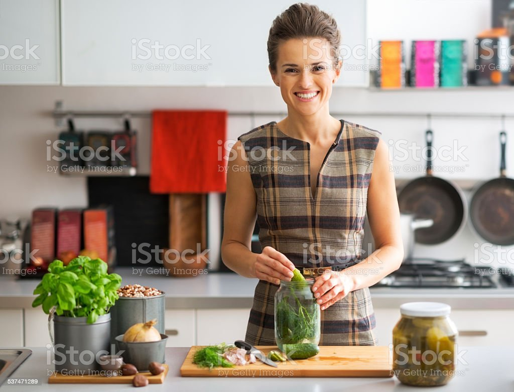 portrait of happy young housewife pickling cucumbers in kitchen stock photo