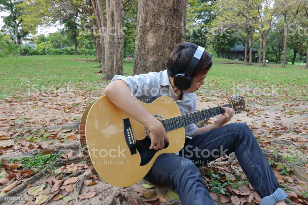 Portrait of happy young man playing acoustic guitar and leaning a tree at the outdoor park. stock photo