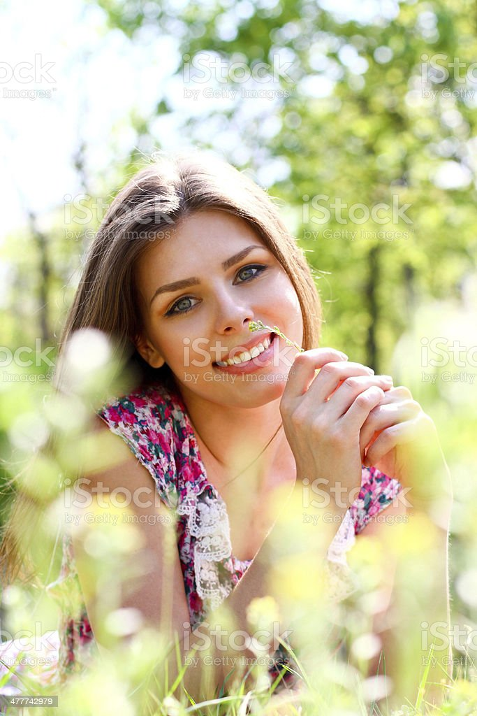 Portrait of happy young woman lying in meadow on warm royalty-free stock photo