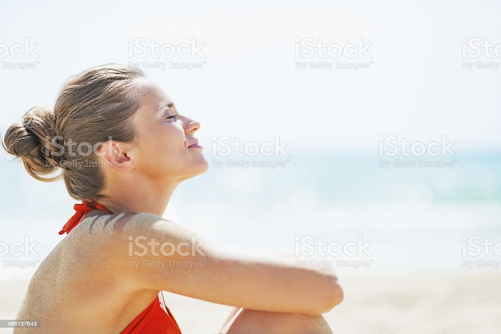 portrait of happy young woman relaxing on beach stock photo