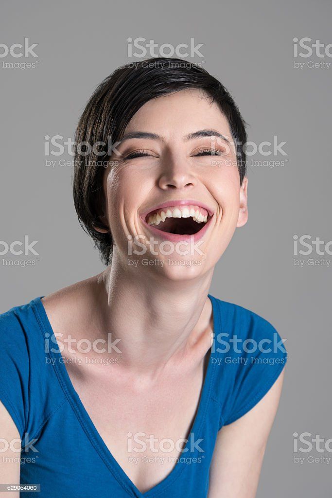 Portrait of heartily laughing young cheerful woman with open mouth stock photo