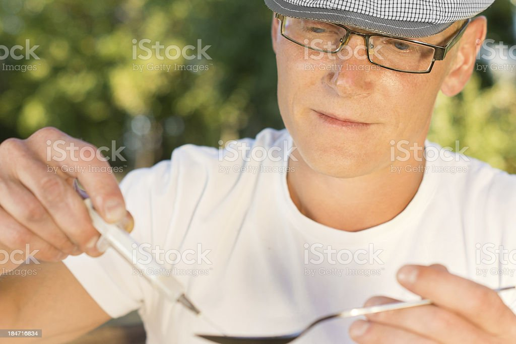 Portrait of heroin consumer filling a syringe royalty-free stock photo