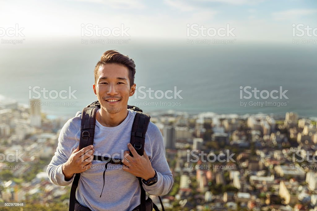 Portrait of hiker smiling against sea stock photo