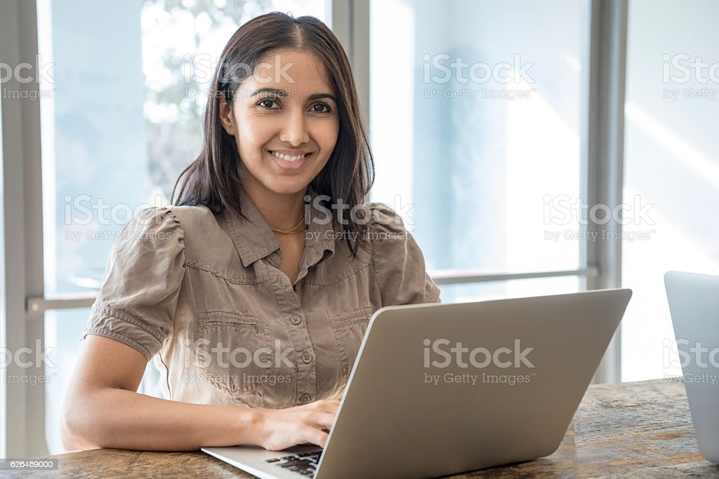 Portrait of Hispanic businesswoman using laptop and smiling stock photo