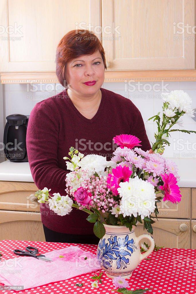 Portrait of housewife arranging decorative flowers stock photo