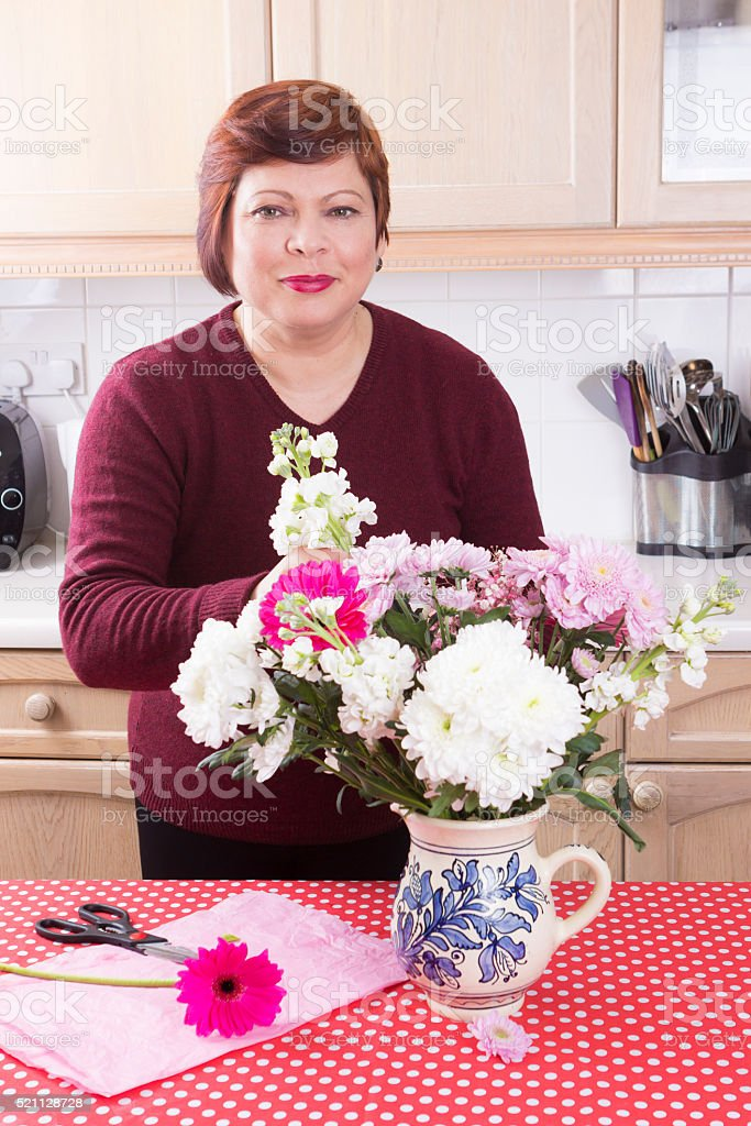 Portrait of housewife arranging decorative flowers stock photo