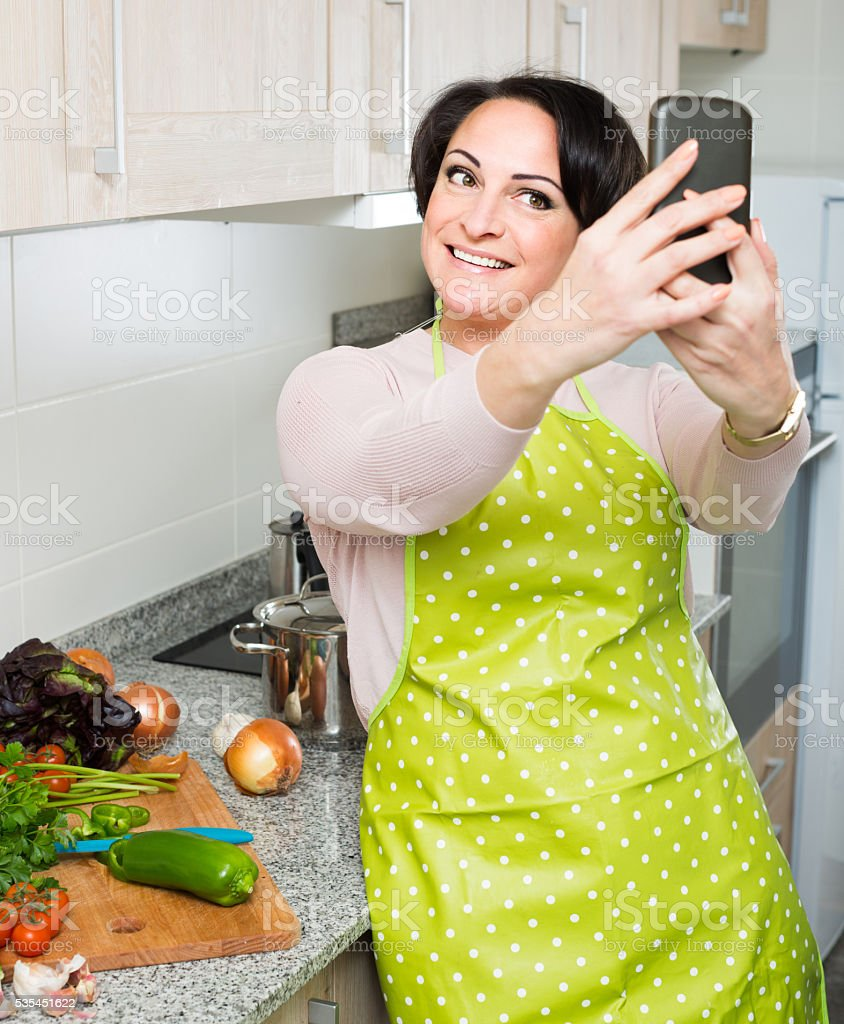 Portrait of housewife in apron making selfie in domestic kitchen stock photo