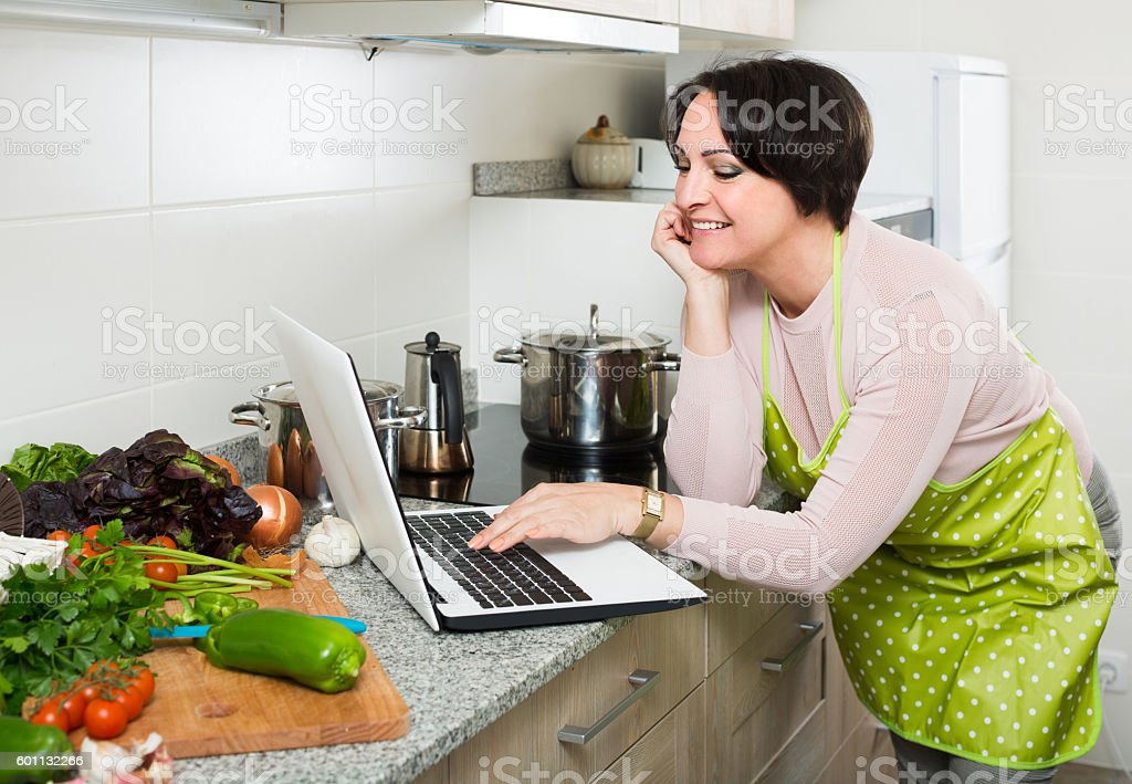 Portrait of  housewife in apron with laptop at kitchen stock photo