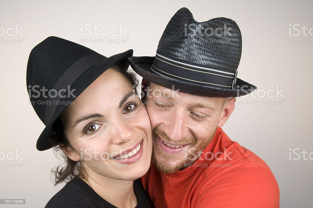 Portrait of hugging, happy couple wearing black hats.  royalty-free stock photo