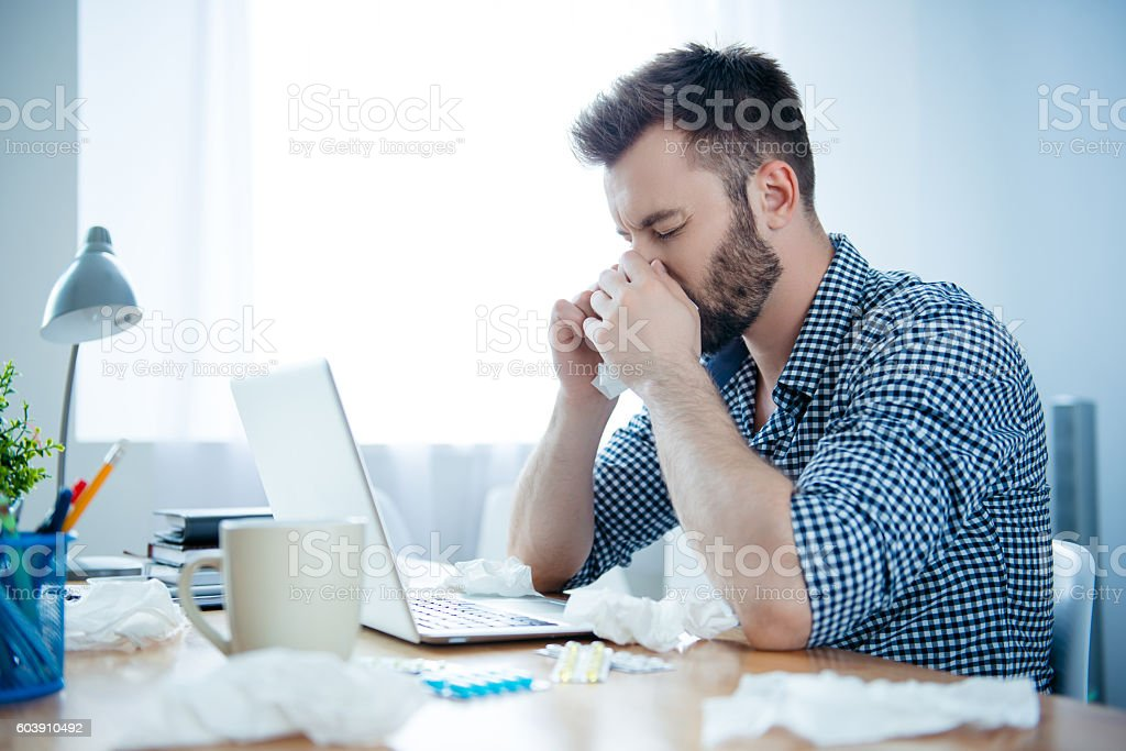 Portrait of ill businessman with fever and running nose stock photo