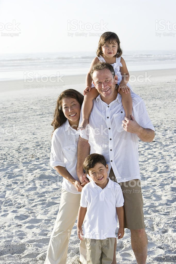 Portrait of interracial family with two children on beach royalty-free stock photo