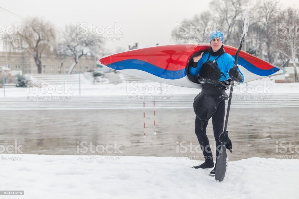 Portrait of kayaker on snow holding his boat stock photo