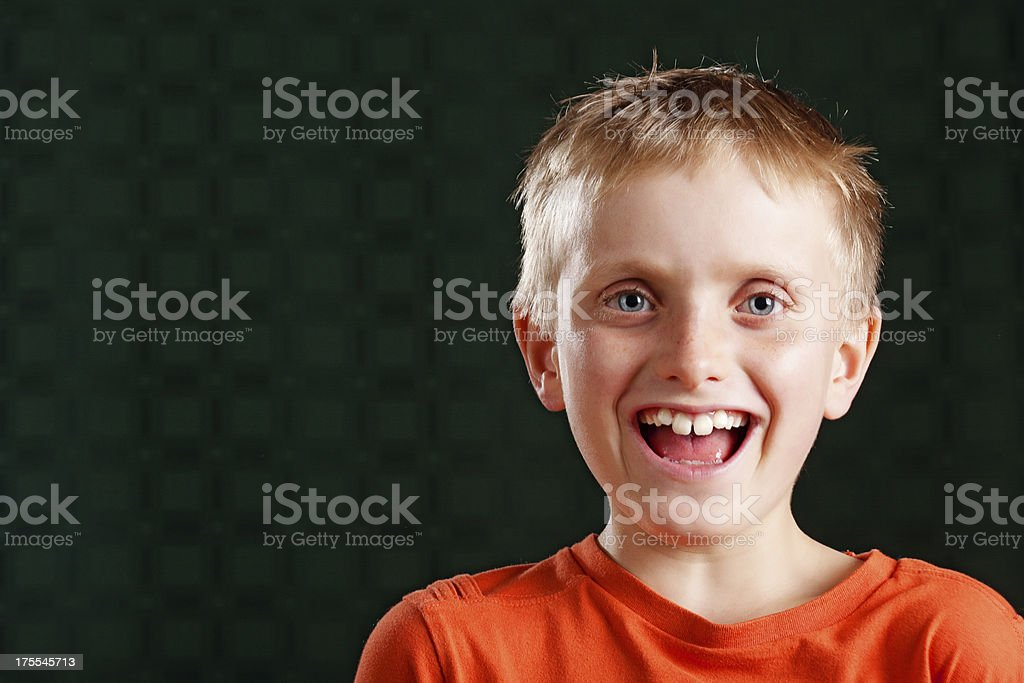 Portrait of laughing 9 year od boy on black royalty-free stock photo