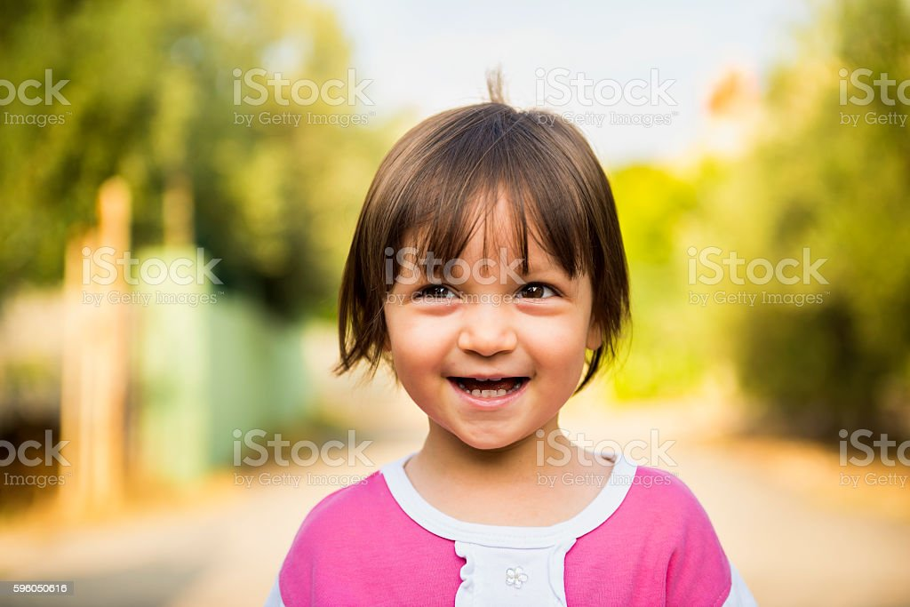 Portrait of laughing baby girl looking away with content smile stock photo