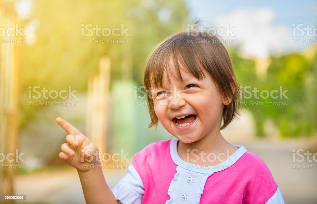 Portrait of laughing baby girl pointing somewhere with content s stock photo