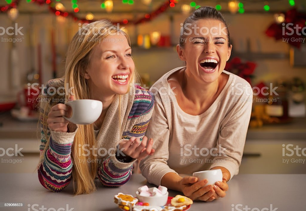 Portrait of laughing girlfriends having christmas snacks stock photo