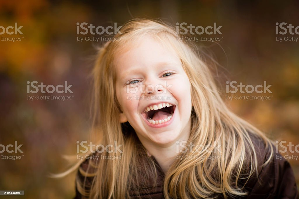 Portrait of Laughing Little Girl Outside on Fall Day stock photo