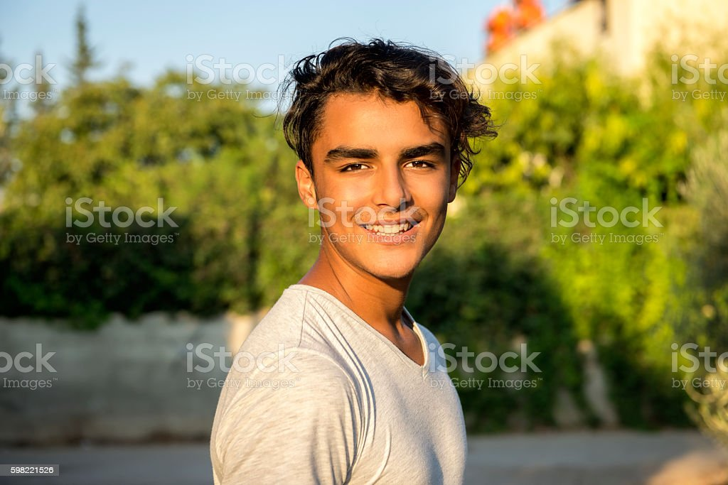 Portrait of laughing young man looking at camera in park stock photo