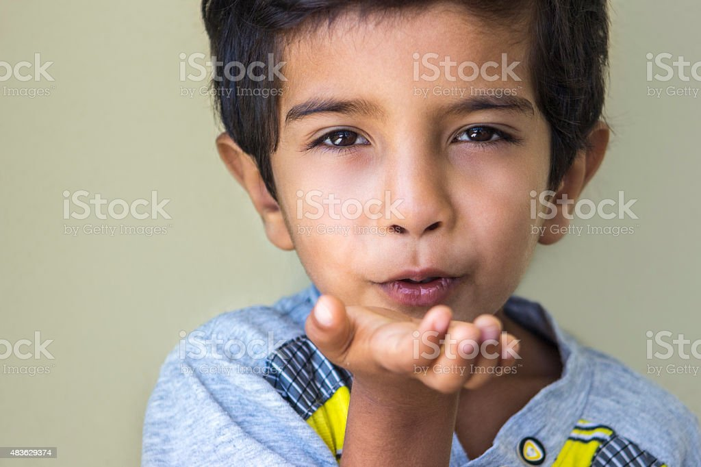 Portrait of liitle boy blowing a kiss stock photo