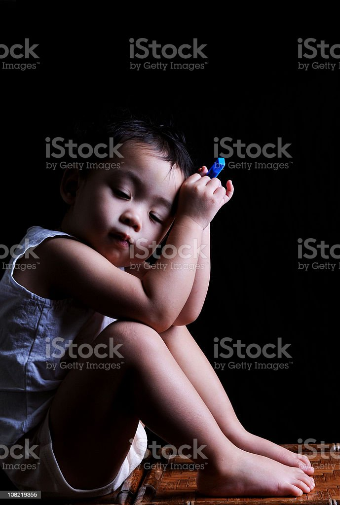 Portrait of Little Asian Boy Sitting Down and Closing Eyes stock photo
