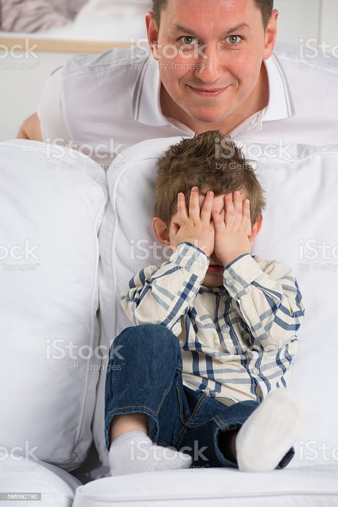 Portrait of little boy closing eyes with his hands stock photo
