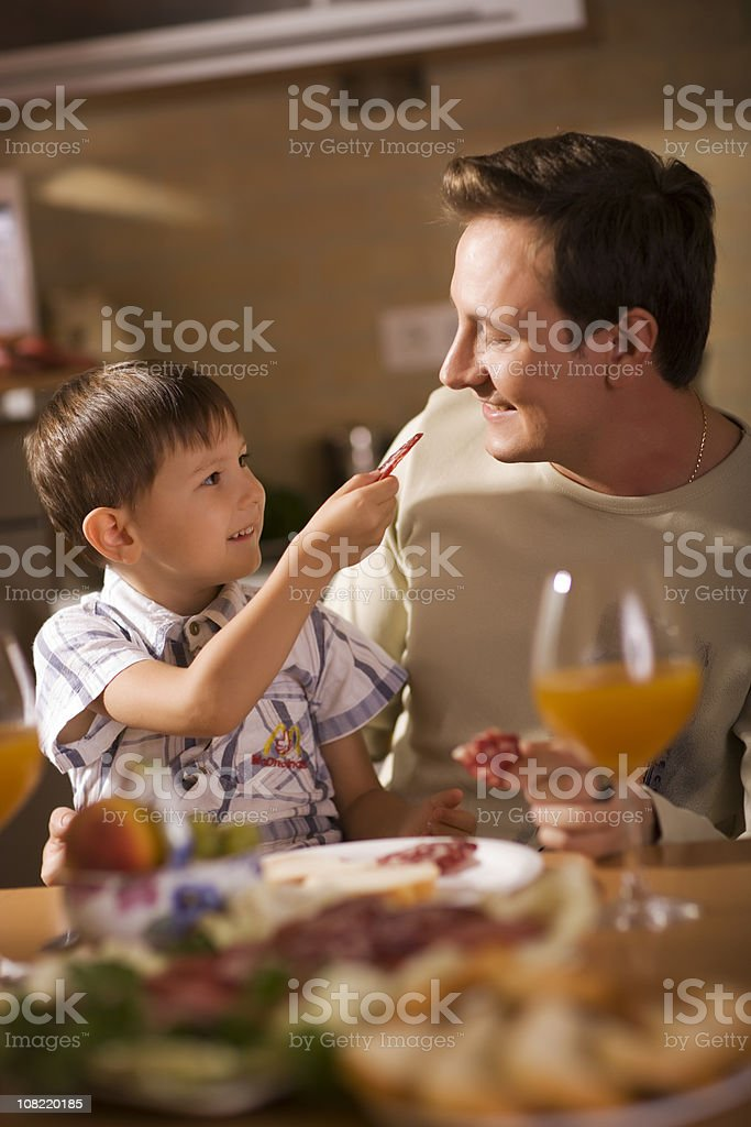 Portrait of Little Boy Feeding Father at Table royalty-free stock photo