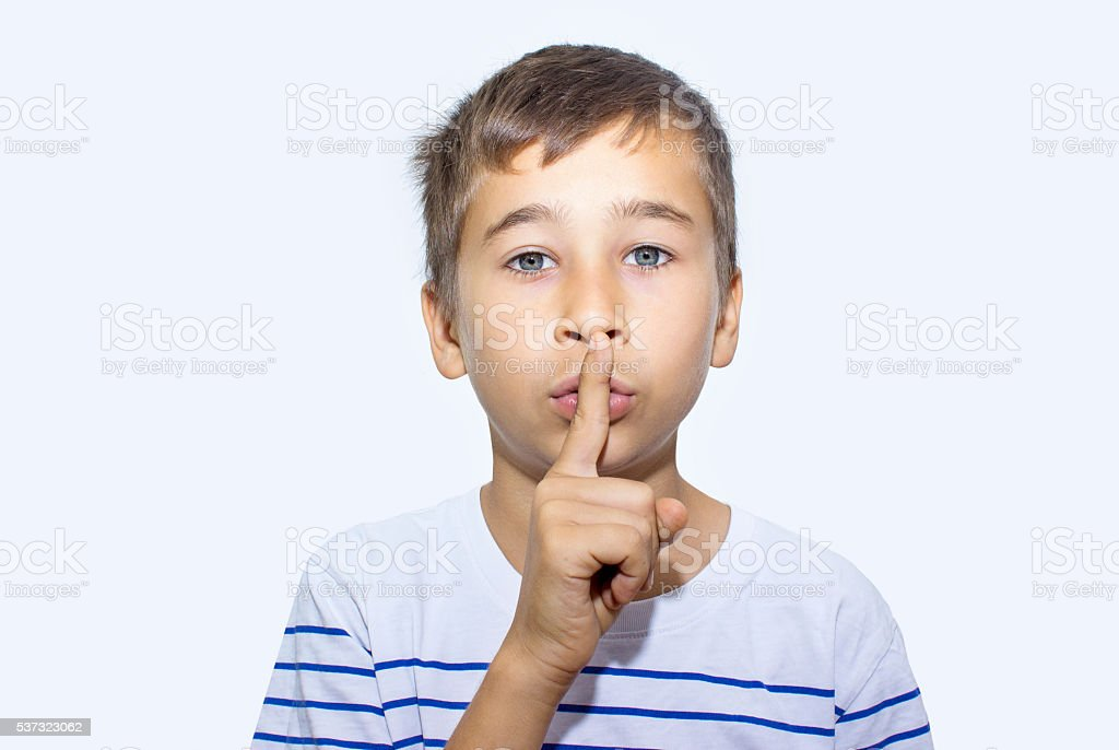 Portrait of little boy gesturing hush sign with his hand stock photo