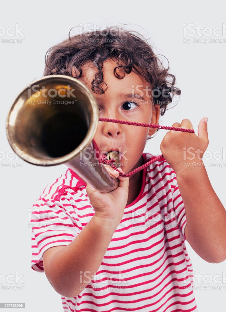 Portrait of little boy playing bugle stock photo