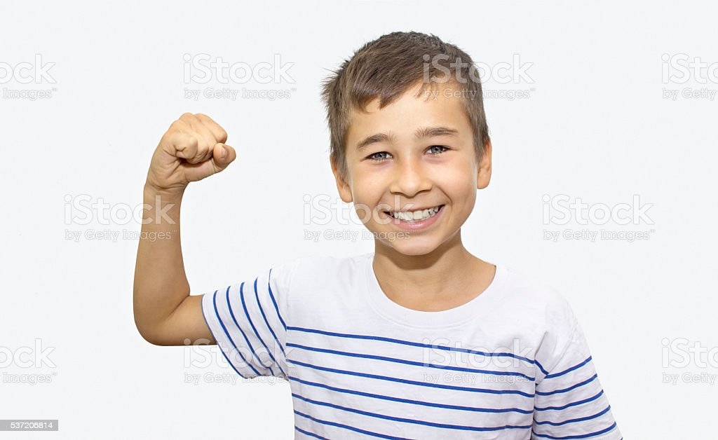 Portrait of  little boy showing his bicep over white background stock photo
