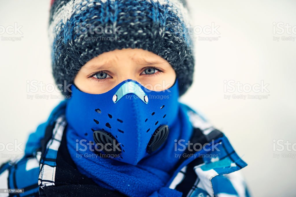Portrait of little boy wearing modern pollution mask stock photo