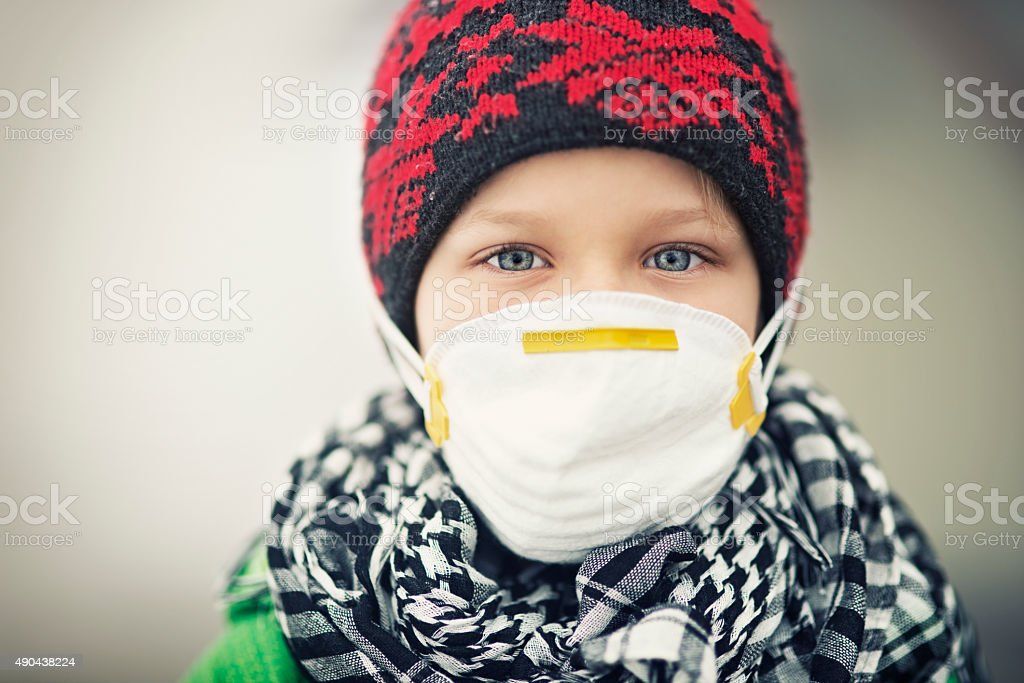 Portrait of little boy wearing pollution mask stock photo