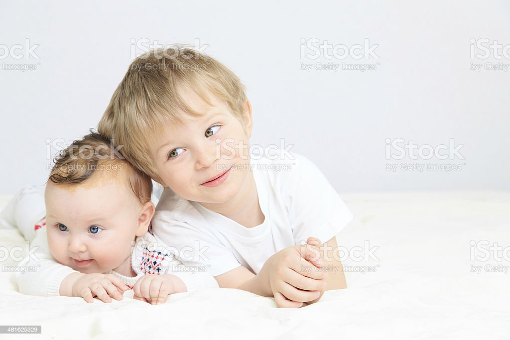 portrait of little boy with newborn sister stock photo
