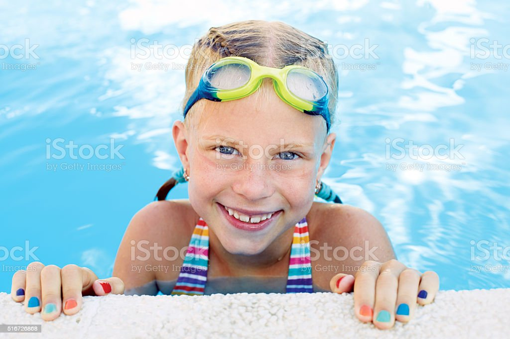 Portrait of little cute girl in the swimming pool. stock photo