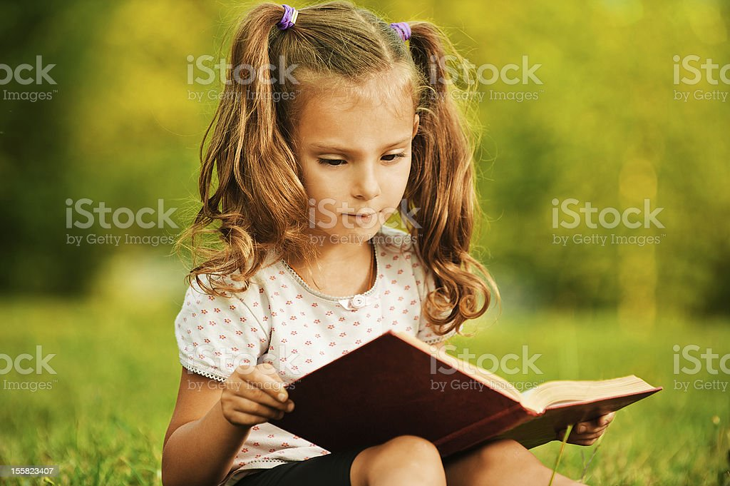 portrait of little cute girl reading book royalty-free stock photo