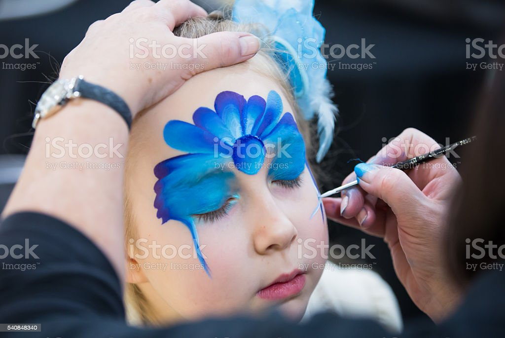 Portrait of little girl during the face painting session stock photo