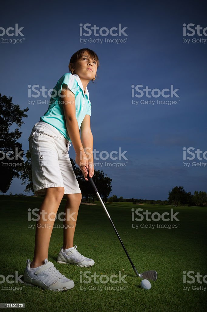 Portrait of little girl hitting golf ball on course royalty-free stock photo
