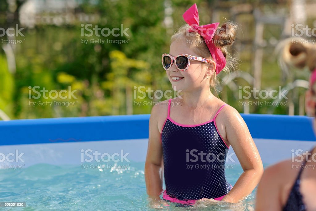 portrait of little girl in tropical style in a swimming pool royalty-free stock photo
