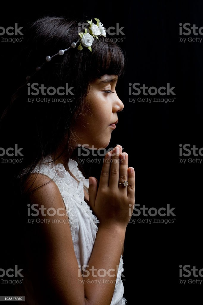 Portrait of little girl praying in dark royalty-free stock photo