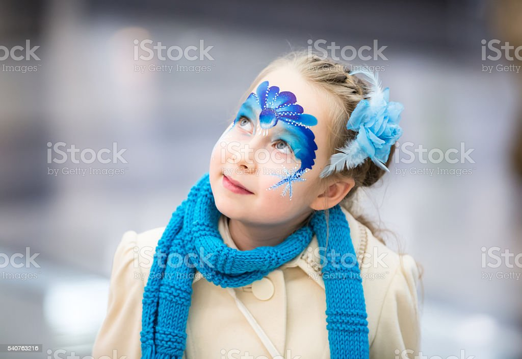 Portrait of little girl with Christmas face painting design stock photo