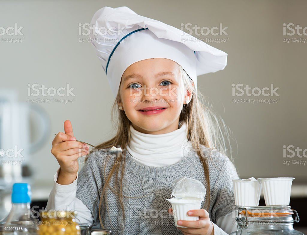 Portrait of little girl with white sour cream indoors stock photo