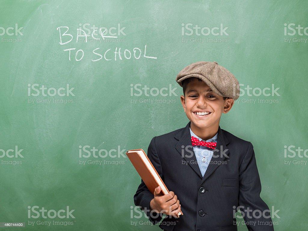 Portrait of little schoolboy posing in classroom stock photo