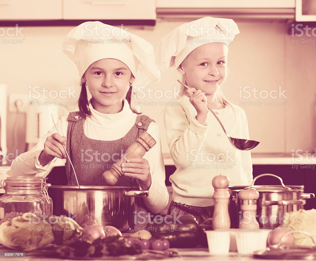 Portrait of little sisters at kitchen   stock photo