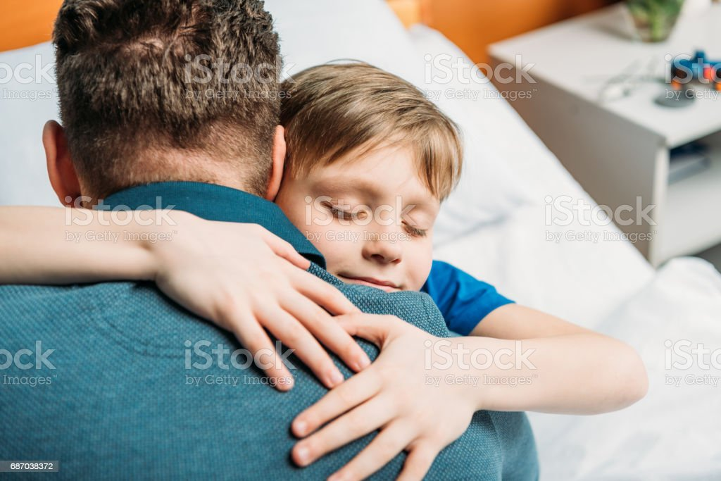 portrait of little son hugging father in hospital chamber stock photo