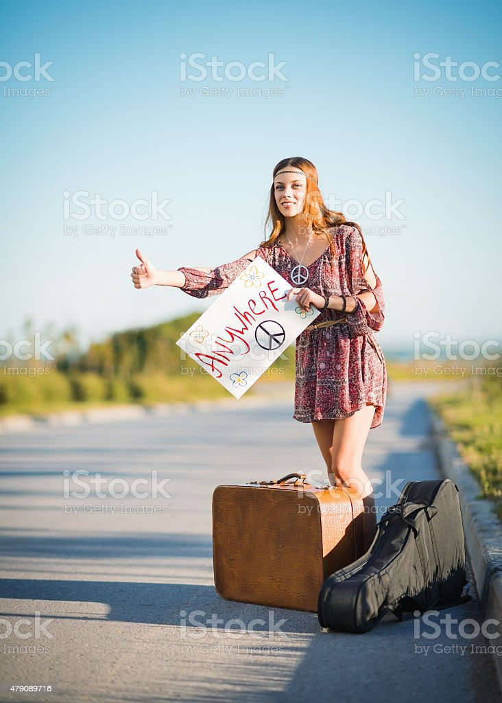 Portrait of lovely young hippie girl hitchhiking on a road stock photo