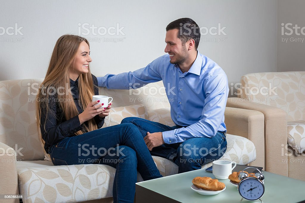 Portrait of lovely young man and woman on the couch stock photo