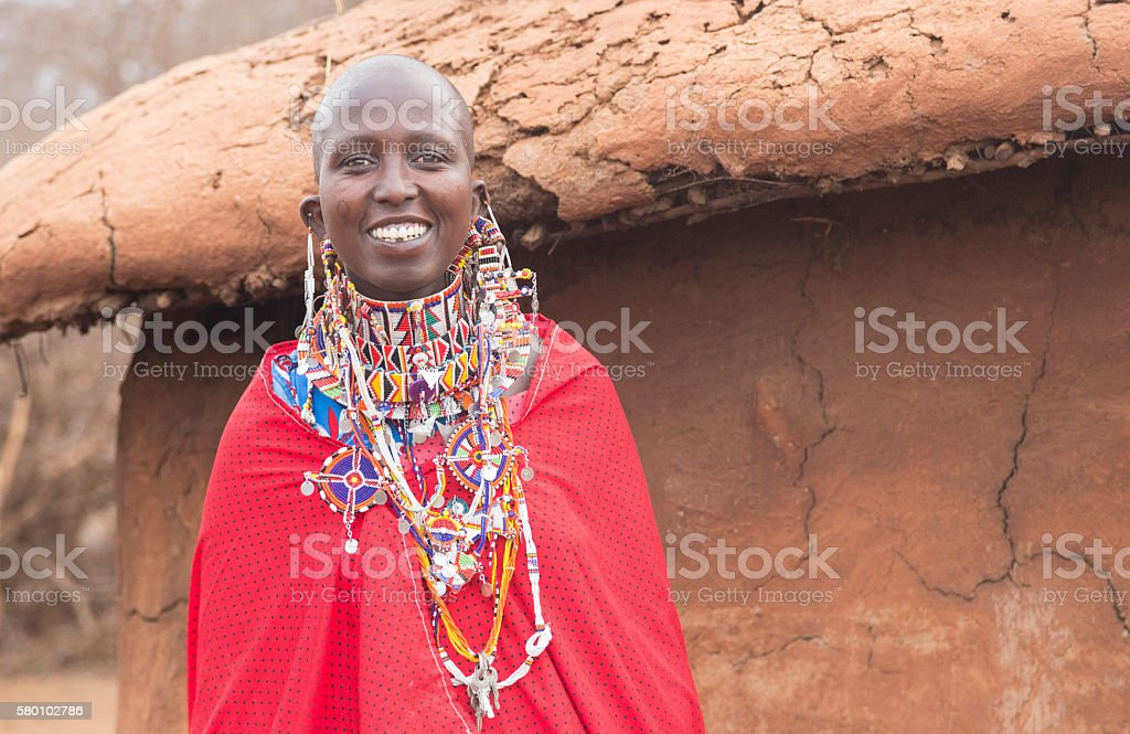 Portrait of Maasai woman in front of hut, Kenya, stock photo