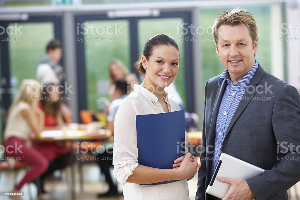 Portrait Of Male And Female Tutors In Classroom stock photo