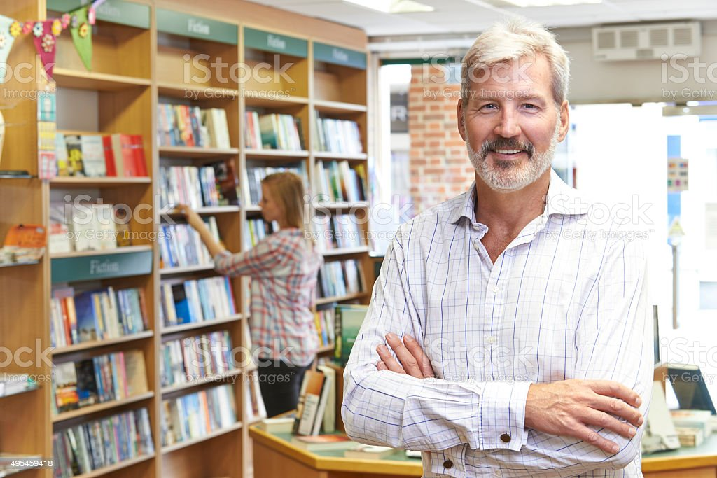 Portrait Of Male Bookstore Owner With Customer In Background stock photo