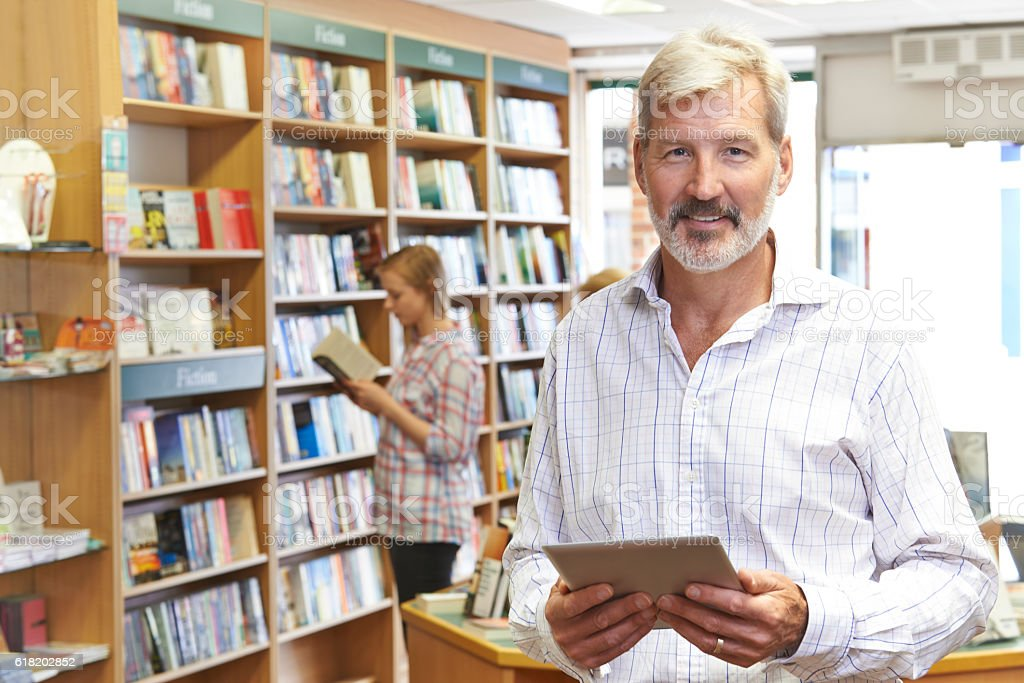 Portrait Of Male Booshop Owner Using Digital Tablet stock photo
